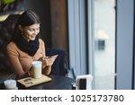 brunette girl using her phone...   Shutterstock . vector #1025173780