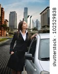 Beautiful business woman standing near her car - stock photo