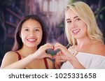 Small photo of Two young women blonde and latin girl smiling and breaking racism idiosyncrasy from a american person and foreign people, both doing a heart sign with teir hands, racism, violence or discrimination