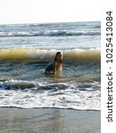 little girl playing in the waves | Shutterstock . vector #1025413084
