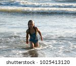 little girl playing in the waves | Shutterstock . vector #1025413120