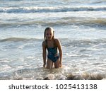 little girl playing in the waves | Shutterstock . vector #1025413138