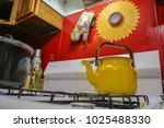yellow tea kettle on stove... | Shutterstock . vector #1025488330