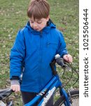 little boy riding a bicycle a... | Shutterstock . vector #1025506444
