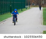 little boy riding a bicycle a... | Shutterstock . vector #1025506450