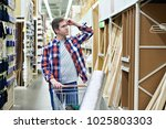 man chooses and buys wooden... | Shutterstock . vector #1025803303