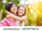 asian and caucasian girl hug... | Shutterstock . vector #1025973670