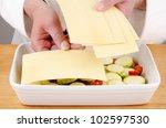 Stock photo female chef fills lasagna dish with prepared lasagne sheets 102597530