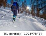 ski de alpinism. woman climbs... | Shutterstock . vector #1025978494
