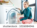 Small photo of shocked young woman looking at camera while crouching near broken washing machine