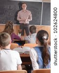 Young male teacher in front of class - stock photo
