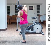 Small photo of sport woman holding painful backache in pain on the exercise bike at home, injury from accident.
