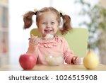 happy child eating porridge... | Shutterstock . vector #1026515908