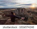 Small photo of Adventurous man sitting with open arms on top of a cliff during a vibrant sunset
