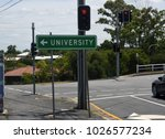 Small photo of Taringa, Brisbane, Australia - February 2018: Road direction sign pointing to University with red traffic signal in background