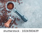 Portafilter with ground coffee, tamper, and coffee beans on a concrete background with copy space. Barista concept from above. - stock photo