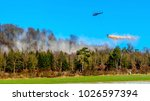 Small photo of A helicopter with a tub on a steel cable distributes lime in the forest to counteract the forest soil acidification, at Marburg in Germany in winter.