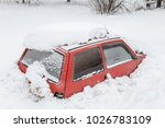 Red Car Under Snow In Snowbank