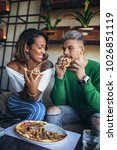 mixed race couple eating pizza... | Shutterstock . vector #1026851119