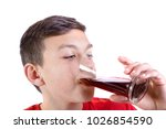 Young caucasian teenage boy drinking a glass of cola drink - stock photo