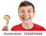 Young caucasian teenage boy eating a scotch egg - stock photo