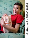 Young caucasian teenage boy watching a scary film - stock photo