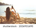 using a smartphone at the beach | Shutterstock . vector #1026931690