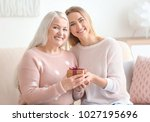 young daughter and mother with... | Shutterstock . vector #1027195696