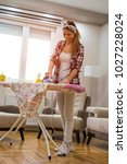 young smiling housewife doing... | Shutterstock . vector #1027228024