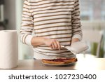 woman wiping knife with paper...   Shutterstock . vector #1027230400
