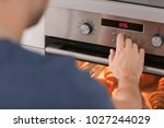 man adjusting electric oven in... | Shutterstock . vector #1027244029