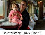 a young mother travels in... | Shutterstock . vector #1027245448