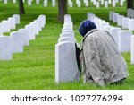 a woman prays at arlington... | Shutterstock . vector #1027276294