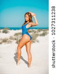 tanned beautiful woman in blue... | Shutterstock . vector #1027311238