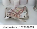 Small photo of money backnote on medicine tray with spatula pill with drug plastic jar on background in payment healthcare hospital cost admit concept