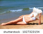 slim woman on a beach. summer... | Shutterstock . vector #1027323154