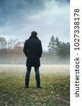 A Man In A Black Coat In Foggy...