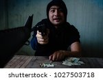 Small photo of The man who is addicted to guns hit a fight. There are drugs, sham drugs, ammunition, Dora on the table.