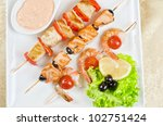 Closeup of grilled salmon and shrimps with tomatoes and peppers on bamboo sticks - stock photo
