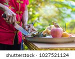 Small photo of Hand of old woman usesing a knife cut food, pox, chicken, fruits for pray and make offering. For luck In various events such as New Year, and a new home, ordained, and marriage.