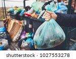 hand with garbage against full... | Shutterstock . vector #1027553278