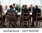 Small photo of Serious multi-ethnic business people team sitting at conference table, senior executives working together with young managers at office staff meeting, focused group negotiations or teamwork concept