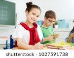 smiling schoolgirl with... | Shutterstock . vector #1027591738