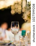 Small photo of clear wine glass on table in dinner table with beautiful bokeh in background.