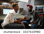 Small photo of Conversation of young deejay with tablet and modern musician discussing new trends in world music
