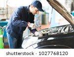 mechanic repairing a car in his ... | Shutterstock . vector #1027768120