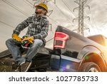 Caucasian Field Worker with Tools. Caucasian Men Wearing Safety Gloves and Hard Hat Seating on the Back of His Pickup Truck. Contractor in the Field - stock photo
