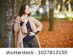 girl in the autumn park leaning ...   Shutterstock . vector #1027813150