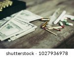 Small photo of Dollars or money with cartridge and drugs on a wood table. It's represent of dangerous, greedy, selfish. It use for background, healthcare or story