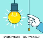 hand turns on light bulb. turn... | Shutterstock .eps vector #1027985860